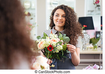 Cheerful beautiful young woman florist holding flower bouquet and looking at the mirror