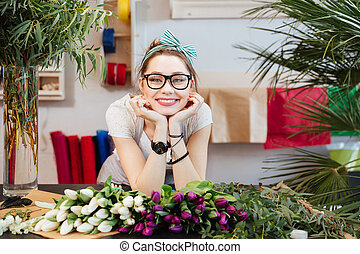 Cheerful beautiful young woman florist selling tulips in flower shop