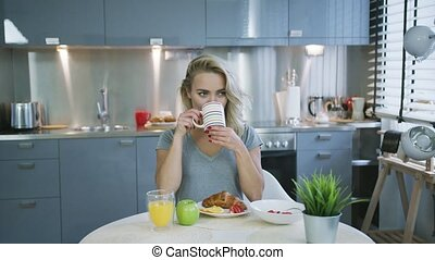 Cheerful woman having good breakfast - Pretty young woman in...