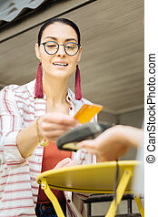 Cheerful woman holding a credit card and paying in a cafe