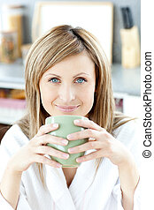 Cheerful woman holding a cup of coffee in the kitchen