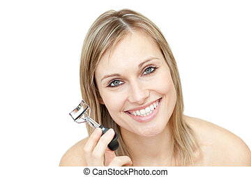 Cheerful woman holding an eyelash curler