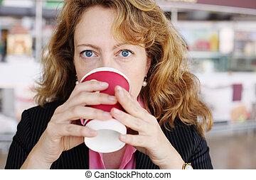 Cheerful woman holding cut of coffee
