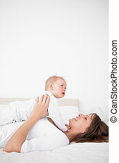 Cheerful woman holding her cute little girl