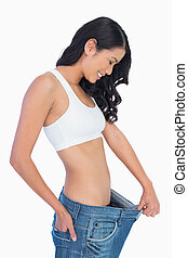 Cheerful woman holding her too big jeans