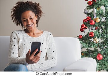 Cheerful woman holding mobile phone on christmas holiday
