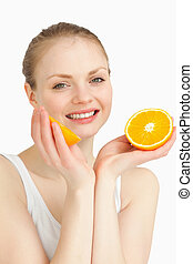 Cheerful woman holding oranges while smiling against white...