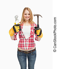 Cheerful woman holding tools