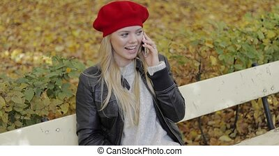 Cheerful woman in beret speaking on phone