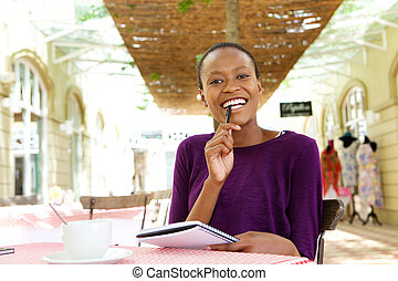 Cheerful woman in cafe making notes