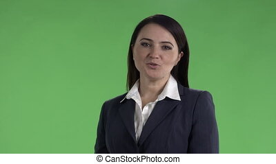 Cheerful woman in dark business suit talking to camera against a green screen