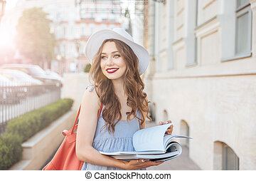 Cheerful woman in hat reading magazines on the street