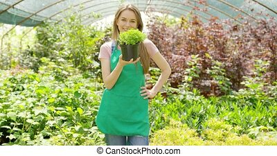 Cheerful woman in hothouse - Smiling young female gardener...