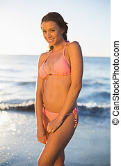 Cheerful woman in pink bikini smiling at camera