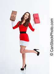 Cheerful woman in santa claus cloth holding gift boxes