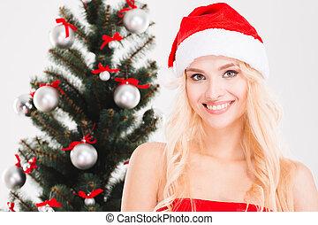 Cheerful woman in santa claus hat posing near Christmas tree