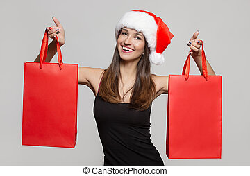 Cheerful woman in santa hat holding shopping bags.