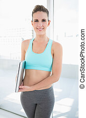 Cheerful woman in sportswear holding laptop