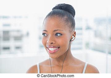 Cheerful woman in sportswear listening to music