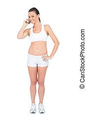 Cheerful woman in sportswear on the phone