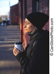 Cheerful woman in the street drinking morning coffee at winter time