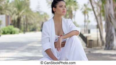 Cheerful woman in white robe laughing outdoors