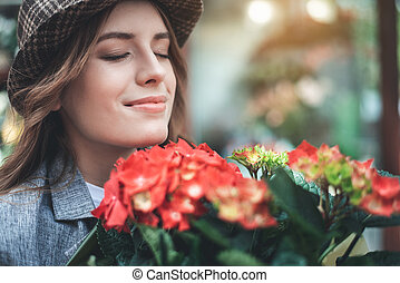 Cheerful woman is enjoying flower aroma outside