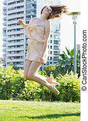 Cheerful woman is playfully jumping in the park