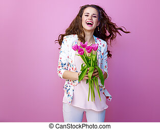 cheerful woman isolated on pink with bouquet of flowers