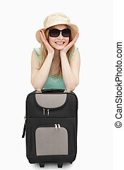 Cheerful woman leaning on a suitcase while sitting