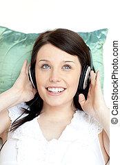 Cheerful woman listening music lying on a sofa