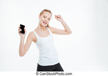 Cheerful woman listening to music from blank screen mobile phone