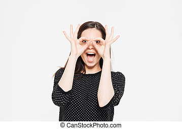 Cheerful woman looking at camera through fingers