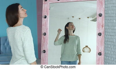 Cheerful woman looking at herself reflection in mirror