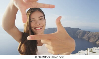 Cheerful young woman making frame with hands. Portrait of female winking while looking through imaginary camera made with fingers. Attractive lady on Santorini, Greece during summer holidays.