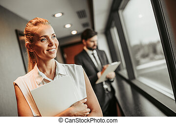 Cheerful woman moving in hall with male