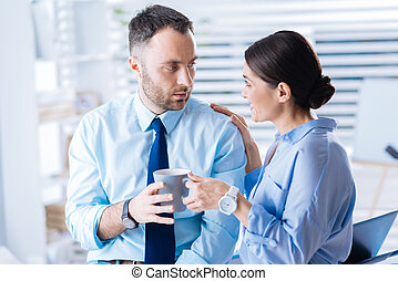 Cheerful woman offering her tired surprised colleague a cup of tasty tea