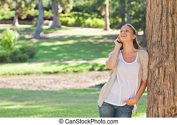 Cheerful woman on the phone leaning against a tree