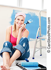 Cheerful woman painting a room