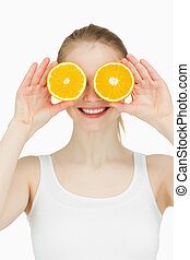 Cheerful woman placing oranges on her eyes against white...