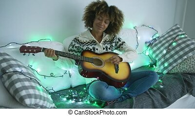 Cheerful woman playing guitar in garland lights - Young...