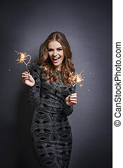 Cheerful woman posing with sparkler