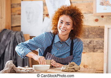 Cheerful woman potter sitting and working in art pottery...