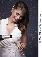 Cheerful woman pouring champagne into the glass