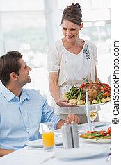 Cheerful woman presenting a roast chicken