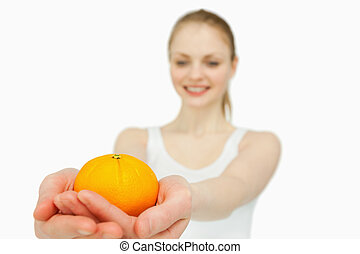 Cheerful woman presenting a tangerine against white...