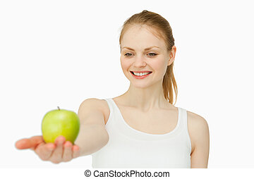 Cheerful woman presenting an apple