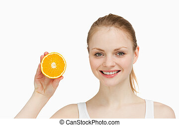 Cheerful woman presenting an orange against white background