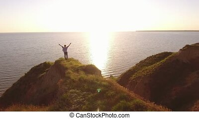 Cheerful woman raises hands standing on the Black Sea coast...