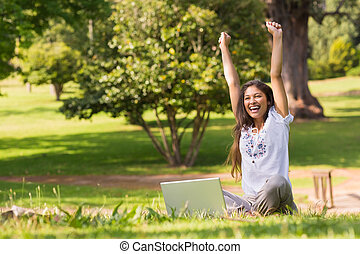 Cheerful woman raising hands with laptop in park - Portrait ...